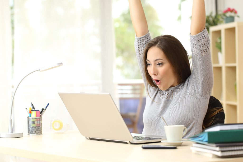 blije vrouw achter laptop